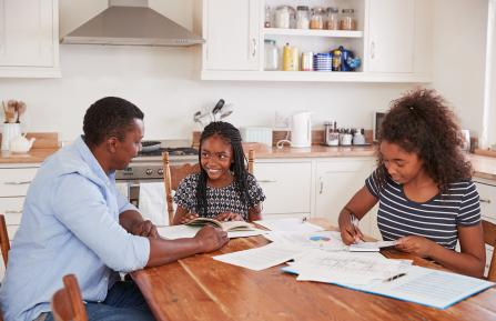 African American father with two daughters working on homework at the kitchen table.