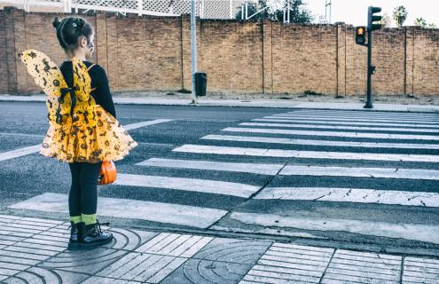 Photo of young girl waiting to cross a street.